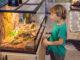Ein kleiner Junge steht vor einem Terrarium aus Glas oder Acryl